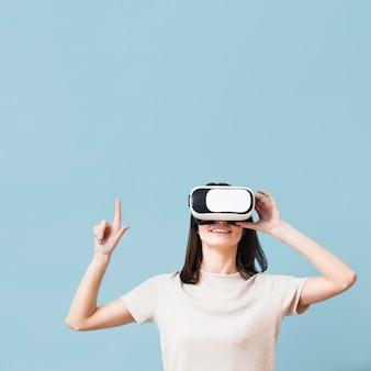 Вид спереди женщины, указывая во время ношения гарнитуры виртуальной реальности