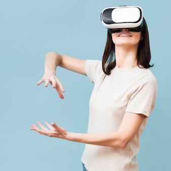 Женщина играет во время использования гарнитуры виртуальной реальности