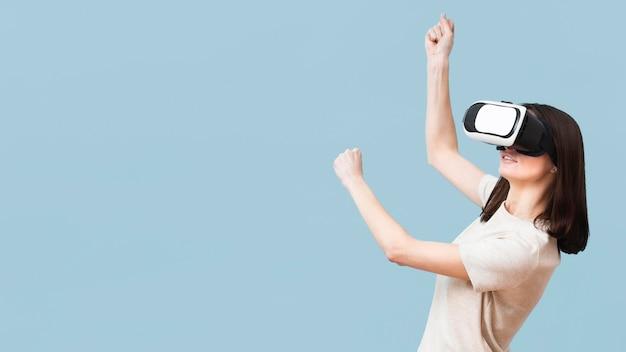 Взгляд со стороны женщины играя используя шлемофон виртуальной реальности