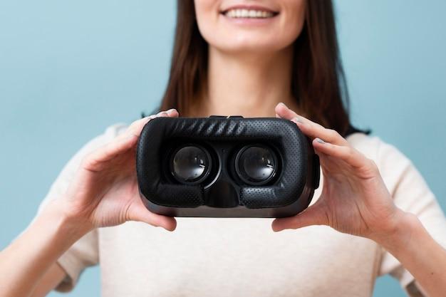 Расфокусированные смайлик женщина, держащая гарнитура виртуальной реальности