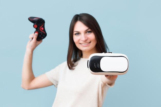 Вид спереди смайлик женщина, держащая гарнитура виртуальной реальности