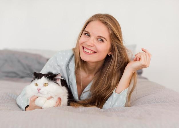 パジャマと猫が付いているベッドで女性の正面図