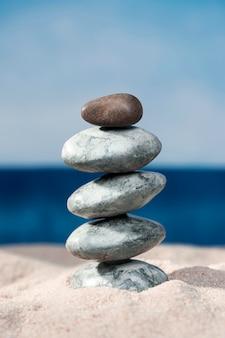 ビーチの砂の上に積み上げられた岩の正面図