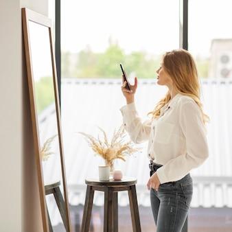 Боковой вид женщина берет зеркальное фото