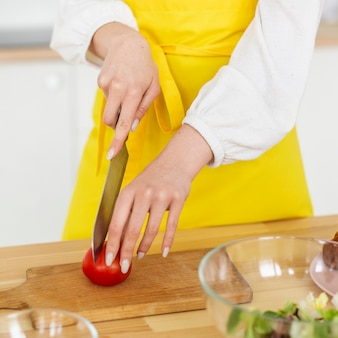 Крупным планом шеф-повар резки помидор