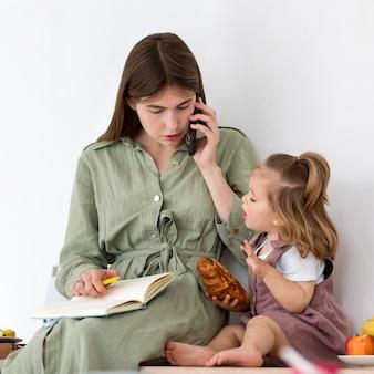 働く母親と一緒に食べる子供