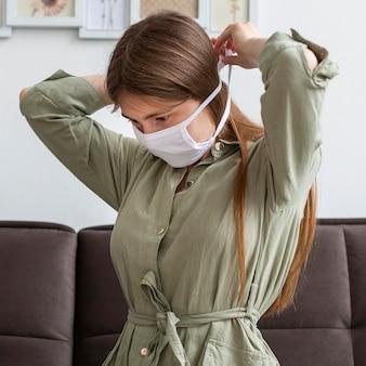 Женщина надевает медицинскую маску
