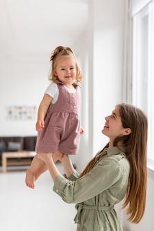 Мать держит дочь в помещении