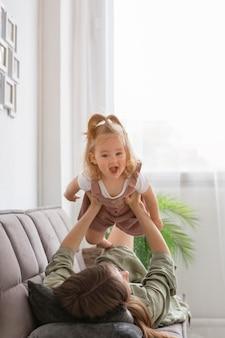 Улыбающаяся девочка играет с мамой