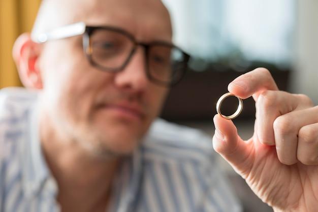 Крупным планом мужчина смотрит на обручальное кольцо