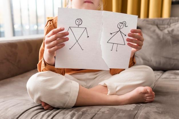 Маленький ребенок держит сломанный рисунок