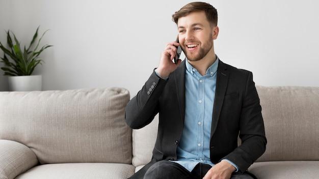 Смайлик деловой человек разговаривает по телефону