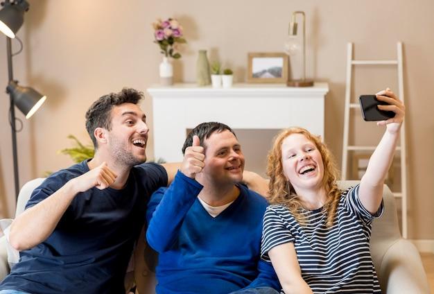 Группа друзей у себя дома, принимая селфи