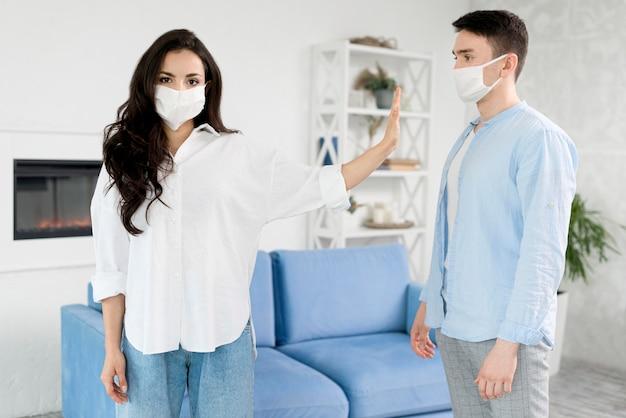 フェイスマスクを持つ男から離れて滞在している女性