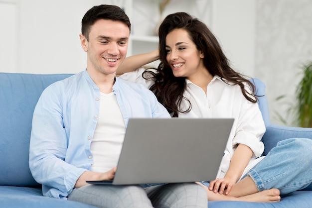 ノートパソコンが付いているソファーで自宅でスマイリーカップル