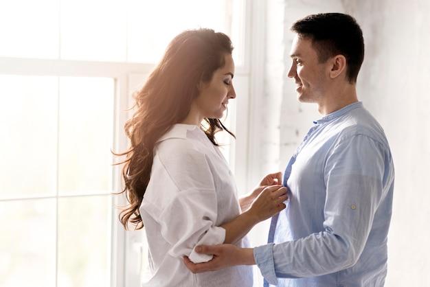 彼のシャツのボタンを押す男を助ける女性の側面図