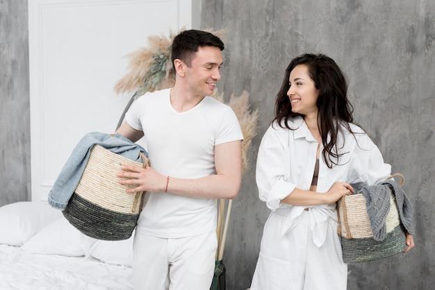 Улыбающаяся пара держит корзины вместе