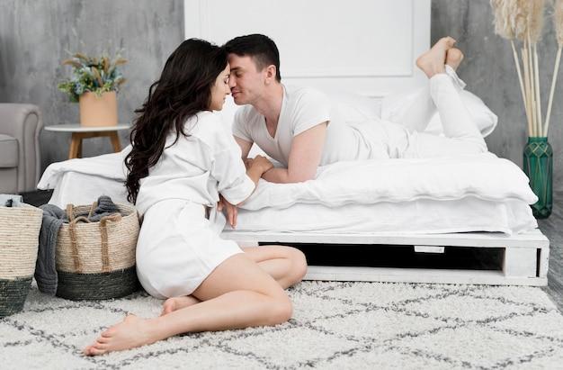 Романтическая пара позирует рядом с кроватью у себя дома