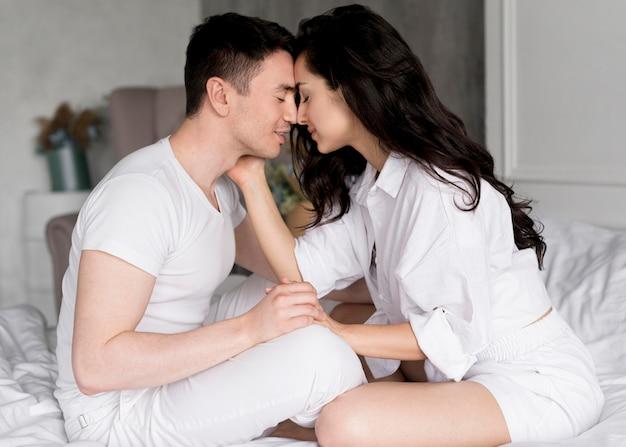 自宅のベッドでロマンチックなカップルの側面図