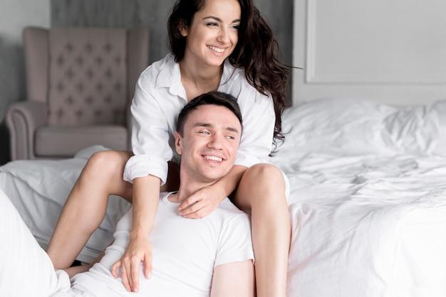 自宅でポーズロマンチックなスマイリーカップルの正面図