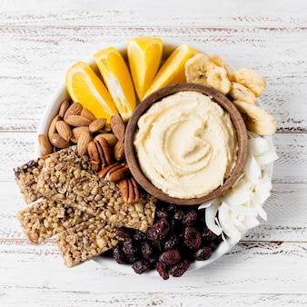 Плоская тарелка с различными орехами и соусом