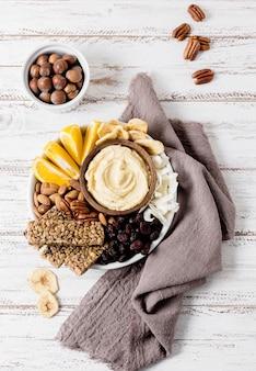 Вид сверху тарелки с ассортиментом орехов и батончиков