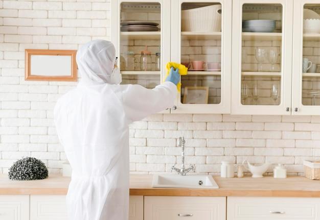 Человек дезинфицирует кухню в защитном костюме