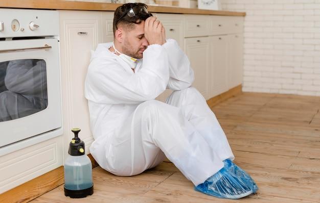 Человек в полный рост сидит на полу на кухне