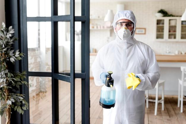 Вид спереди человека с дезинфицирующей бутылкой