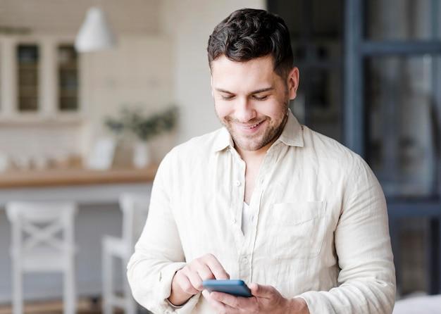 Смайлик мужчина держит смартфон