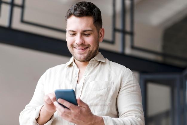 Низкий угол мужчина держит смартфон