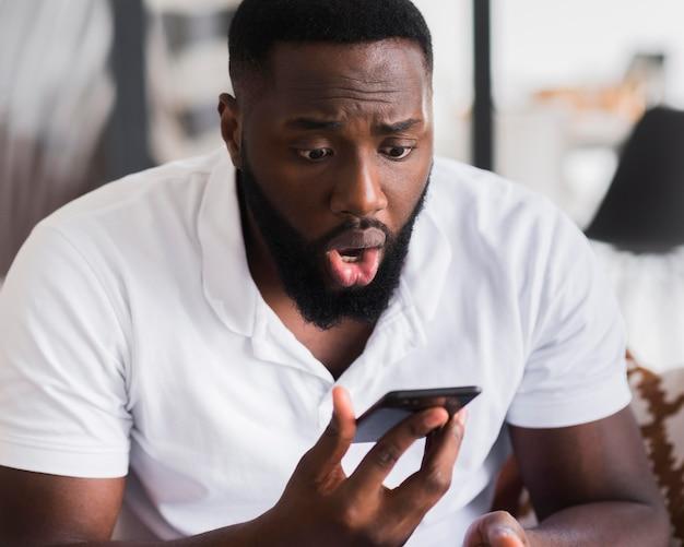 Портрет мужчины удивлен после просмотра своего телефона