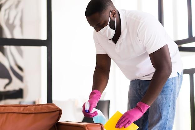Взрослый мужчина дезинфицирует дом спреем