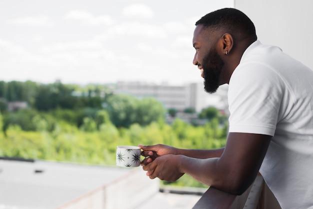 Вид сбоку взрослый мужчина, наслаждаясь видом из дома