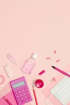 Выше вид школьных предметов на розовом фоне