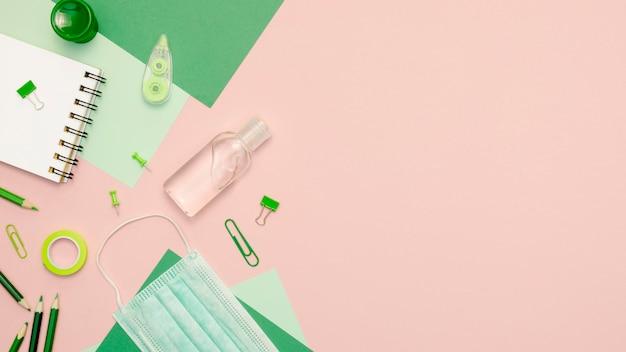 Вид сверху зеленые принадлежности на розовом фоне