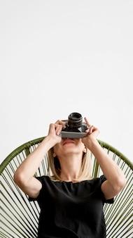 椅子に座って写真を撮る女性