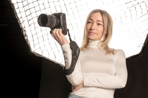 Женский фотограф держит ее камеру