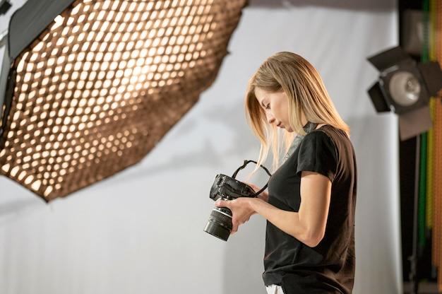 スタジオで横向きの女性写真家