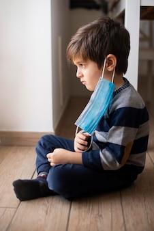 医療用マスクを持った少年のポートレート