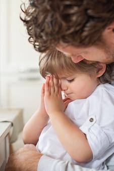 子供と一緒に祈る父