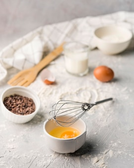 テーブルの上に卵とベーキング小麦粉を入れた泡立て器