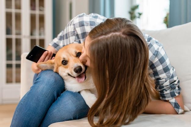 Женщина держит смартфон и целует ее собаку