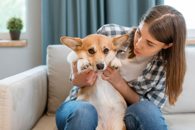 Вид спереди женщины на диване со своей собакой