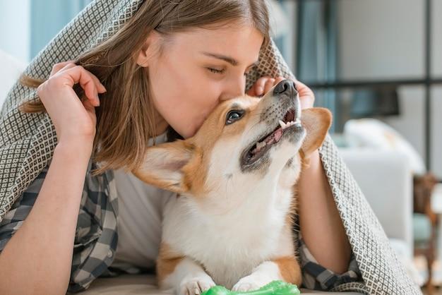 女性が彼女の愛らしい犬にキス