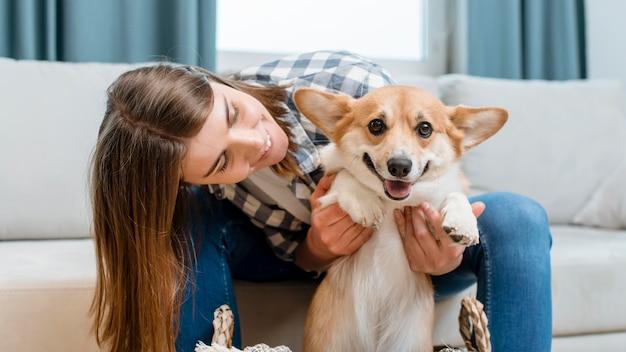 彼女のかわいい犬を保持している女性の正面図