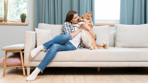 彼女のペットの犬とソファの上の女性の正面図
