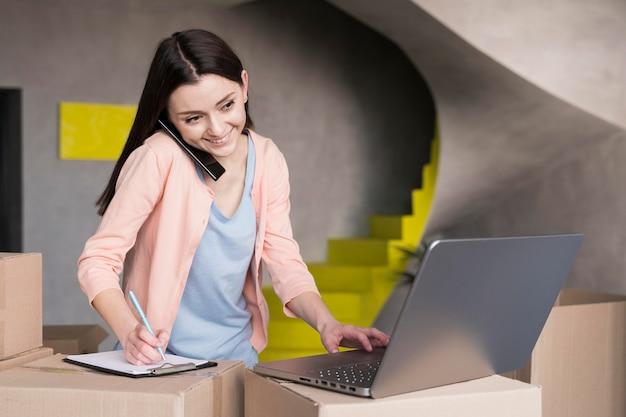 Вид спереди женщины, готовящей поставки из дома, используя ноутбук