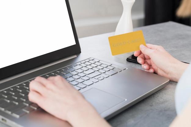 ラップトップに取り組んでいるとクレジットカードを持っている女性