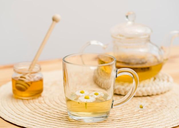 ティーポットと蜂蜜の瓶が付いている高角度ガラス
